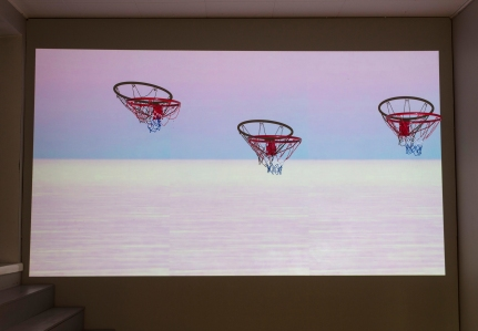 """Auringonnousun hattutemppu (The Hat Trick of Sunrise), 2018 Video installation Size: c. 350cm x 300cm x 50cm Video: 00:59 loop, no sound Materials: Video and basketball hoops Last exhibited in my solo show """"Tässä menee vaan pari minsaa (This will only take a couple of minutes""""), Galleria Lapinlahti, Helsinki (Sept-Oct. 2018). Pictures by Iida-Liina Linnea"""