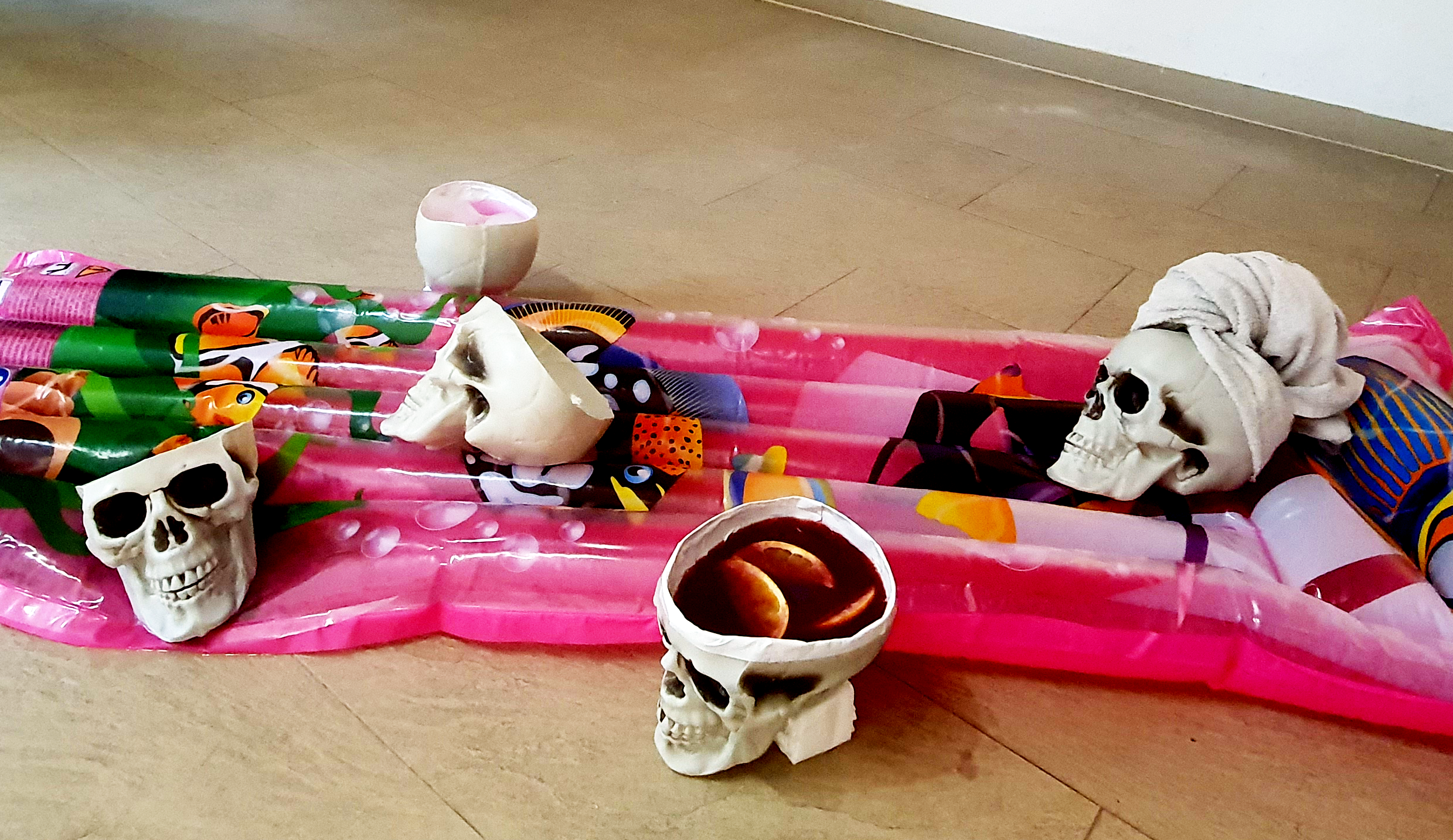 Summertime and the Living is Easy, 2019. Plastic skulls filled with sangria, sand, shampoo, a towel and nothing, relaxing on an inflatable pool float. Size: 180cm x 90cm.